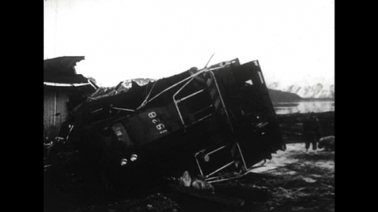 ALASKA 1960s: An overturned train catches on fire as a twister hits.