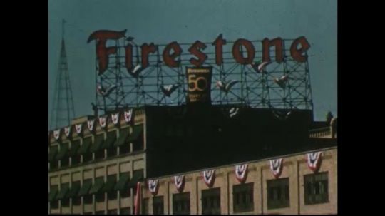 UNITED STATES 1950s: Firestone plant, close up of sign / Plant exterior / Plant entrance / View of clock tower, banner / Plant exterior.