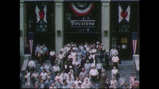 UNITED STATES 1950s: Workers leaving Firestone plant / Low angle view of workers / View of banner on plant.