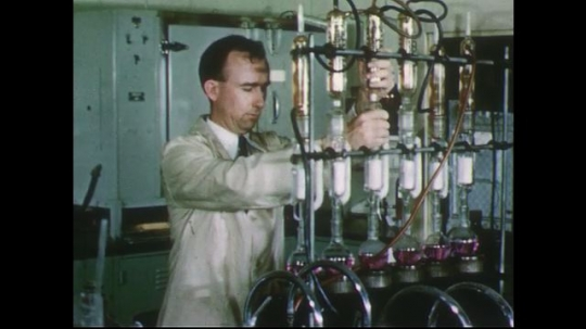 UNITED STATES 1950s: Scientist in lab adjusts equipment.
