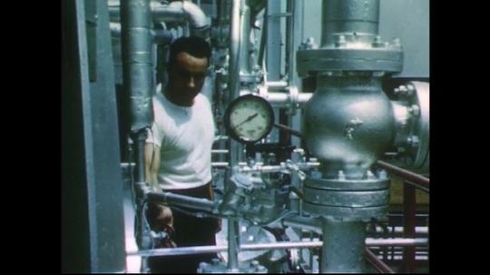 UNITED STATES 1950s: Man in factory adjusts valve / Long shot of man, pipes.