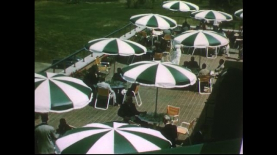 UNITED STATES 1950s: High angle view of patio / Men eat at tables / Men talk at table.