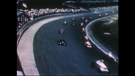 UNITED STATES 1950s: High angle view of car race / Cars on track / Cars drive past crowd / Pan of car on track / Pan from driver to wheel / Close up of tire on track.