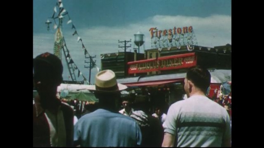 UNITED STATES 1950s: View of crowd at circus, Firestone factory in background / Pan from crowd to circus tent.