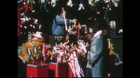 UNITED STATES 1950s: Family at circus, man gives toys to boys / Man at booth gives puts hat on girl.