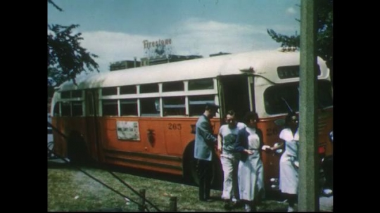 UNITED STATES 1950s: People exiting bus, Firestone plant in background / Driver ushers kids off bus / Families enter circus.
