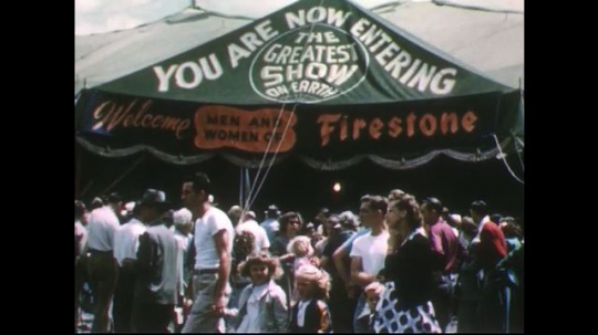 UNITED STATES 1950s: Crowd in front of Firestone circus tent / Families walk into circus tent.