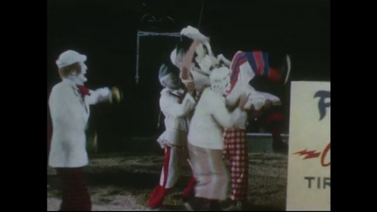UNITED STATES 1950s: Clowns perform at circus, clown lifted into box / Box shoots smoke, clowns run out / Clowns walk in circus ring