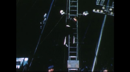 UNITED STATES 1950s: Man climbs up ladder at circus.