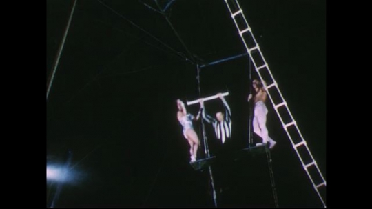 UNITED STATES 1950s: Low angle view of man swinging on trapeze / Woman swings on trapeze.
