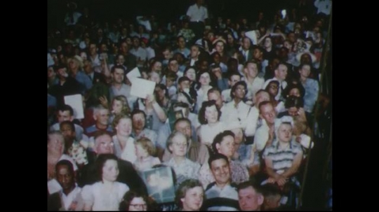 UNITED STATES 1950s: Audience in stands at circus / Views of acrobats performing tricks on trapeze.