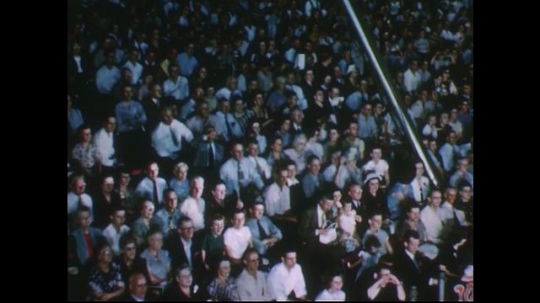 UNITED STATES 1950s: Audience in stands at circus / Woman balancing on trapeze, swings back and forth.