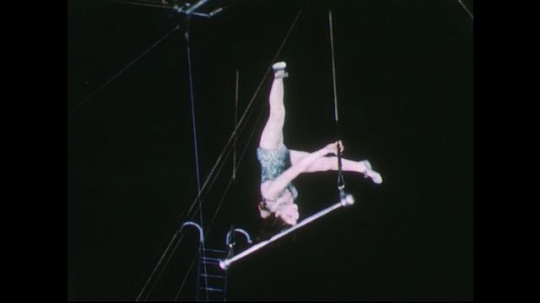 UNITED STATES 1950s: Woman balances on her head on trapeze / View of audience / Woman climbs down ladder.