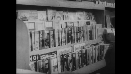 UNITED STATES 1950s: Tilt down from magazine rack to stack of newspapers, zoom out, men take newspapers, walk and talk.