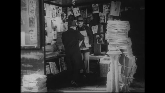 UNITED STATES 1950s: Man hands newspaper to customer in newsstand, man walks in / Pan of newspaper stacks.