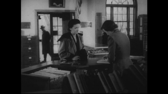 UNITED STATES 1950s: Interior of library, woman checks out book, man walks in.