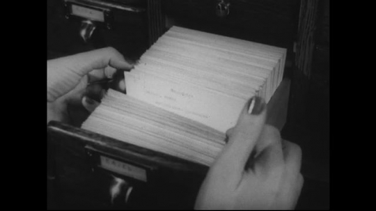 UNITED STATES 1950s: Hands look through library cards / Hand takes pamphlet from stack / Hand pulls book from shelf.