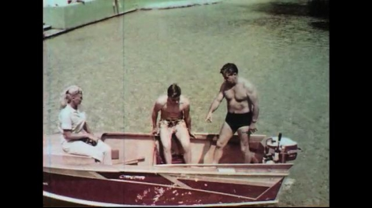 UNITED STATES 1960s: Family in boat, father gives instruction to son, picks up equipment.