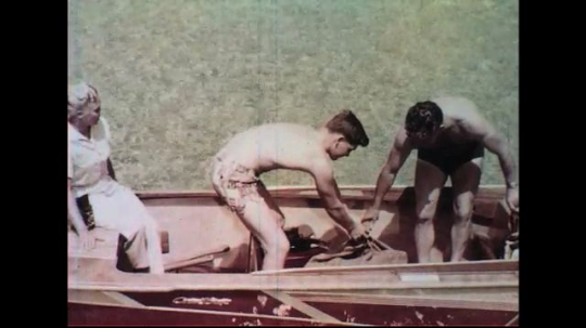 UNITED STATES 1960s: Father and son in boat, boy cuts finger, man looks at cut.