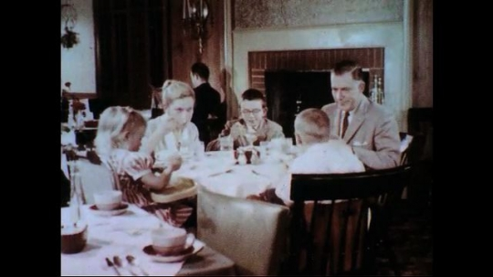UNITED STATES 1950s-1960s : A family converses as it eats dessert at a restaurant.