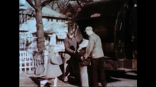 UNITED STATES 1950s-1960s : Garbage collectors place trash into their truck as a girl watches.