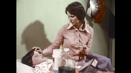 UNITED STATES 1970s: Mother with sick boy, boy takes medicine.