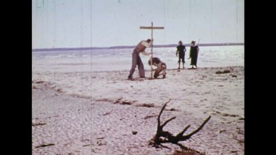 UNITED STATES 1600s: Colonists on beach, put cross in sand.