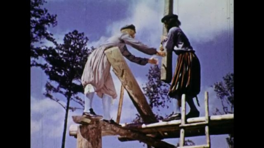 UNITED STATES 1600s: Colonial men put beams on house / Man thatching roof / Men saw board.