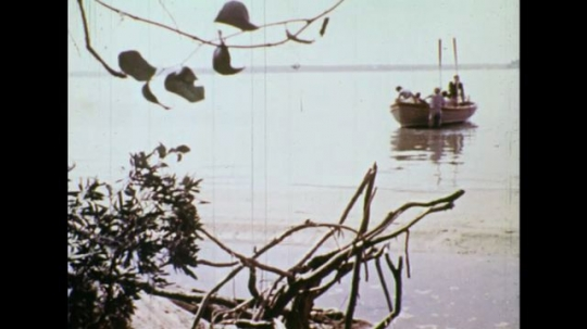 UNITED STATES 1600s: Long shot, boat in harbor, men take supplies from boat / Native Americans in village.