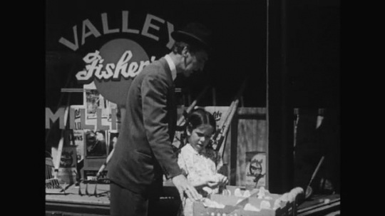 UNITED STATES 1950s: A man and his daughter stand outside a store looking at chicks.