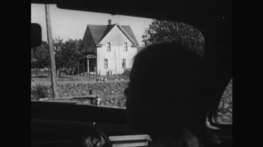 UNITED STATES 1950s: As her father is driving, the young girl watches as their car passes lush greenery.