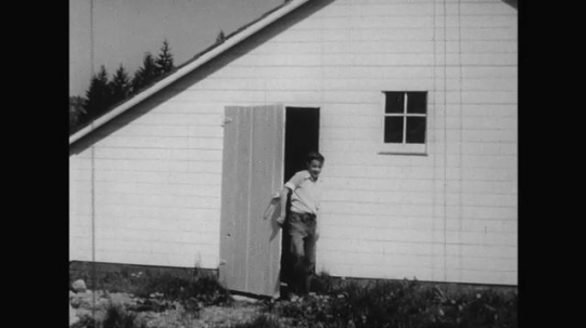 UNITED STATES 1950s: The boy exits the farmhouse and is greeted by the farmer, father, and girl who grabs his hand and brings him inside the farmhouse again.