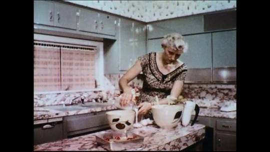 UNITED STATES 1950s: A woman preparing her ingredients to bake is bothered by a fly.