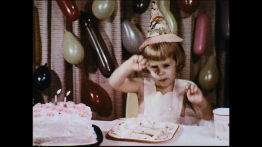 UNITED STATES 1950s: A birthday girl eats her cake while trying to ward off a fly which leads to her tummy ache and crying later on.