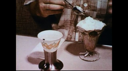 UNITED STATES 1950s: A man removes a house fly stuck on his dessert and proceeds to eat it.