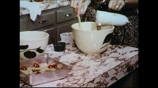 UNITED STATES 1950s: A woman preparing her baking mix stops to swat a fly on the table.