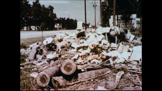 UNITED STATES 1950s: Trash accumulates on a roadside dump as cars pass by the road.