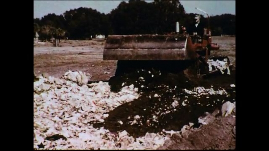 UNITED STATES 1950s: A bulldozer covers the trash at the municipal dump as other trash is burned using huge incinerators.