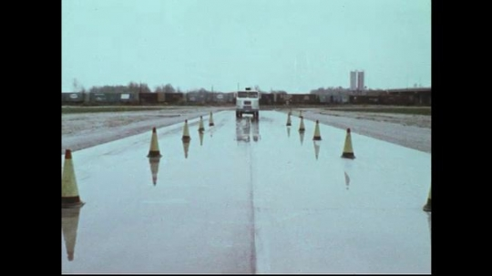 UNITED STATES 1970s: Semi truck drives on course / Truck spins and stops / Panning shot of truck driving / Close up of truck wheels.