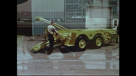 UNITED STATES 1970s: Men position construction equipment / Zoom out of flat tire to man standing by car.
