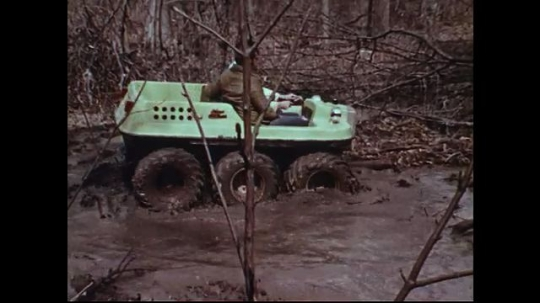 UNITED STATES 1970s: Men in all terrain vehicle, driving through mud / Driving over hill / Driving across stream.