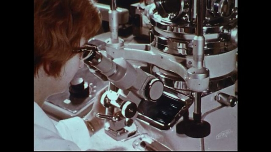 UNITED STATES 1970s: Woman looks through microscope / Close up of factory equipment / Thread going through machine / Close up of thread in machine.