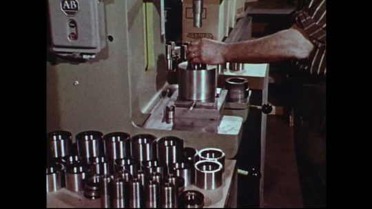 UNITED STATES 1970s: Man using equipment in factory / Montage of views of factory equipment.