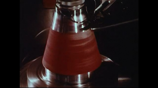 UNITED STATES 1970s: Close up of piece of factory equipment spinning / Zoom out of bowling balls on machine in factory.