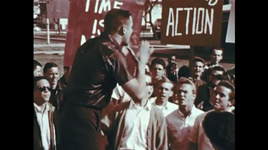 UNITED STATES 1960s: An agitator convinces demonstrators to take physical action for their belief which is immediately responded to by police arriving at a scene.