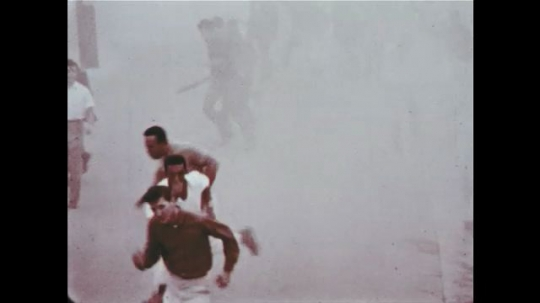 UNITED STATES 1960s: Rioters run away, confused, as tear gas strikes them.
