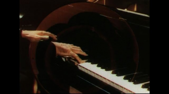 UNITED STATES 1950s: Sound waves superimposed over hands playing piano.