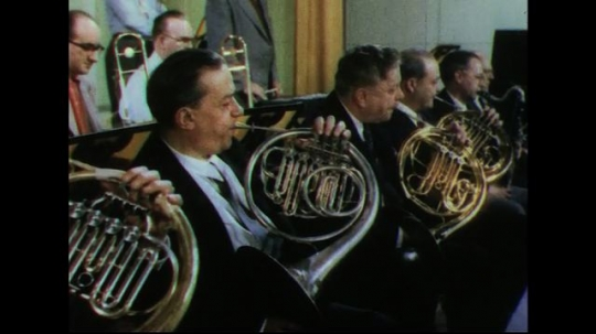 UNITED STATES 1950s: Men in orchestra playing French horns, pan to clarinets, pan to flutists, pull back to show whole orchestra.