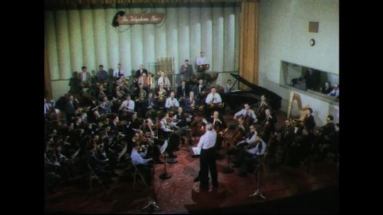 UNITED STATES 1950s: High angle shot of orchestra playing / View of conductor.