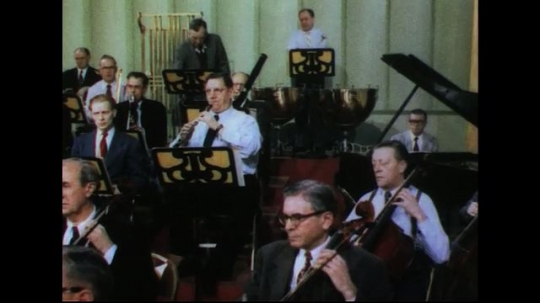 UNITED STATES 1950s: Tilt across orchestra playing / People in sound booth / Engineer with recording equipment, man signals approval.